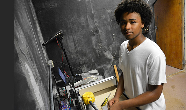 <p>Jacari Renfroe creating a solar powered cell phone charger made from plastic found on Bermuda's beaches.</p>