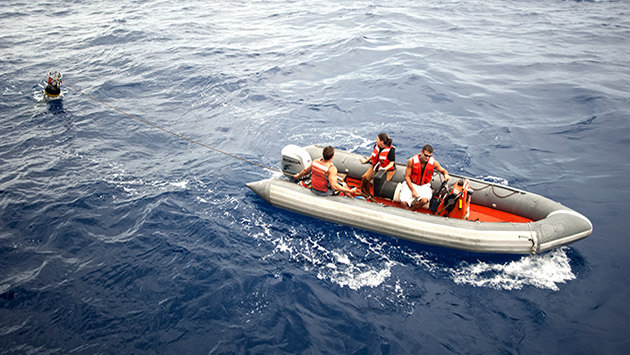 <p> 	Crew members use a rescue boat to recover the HRP and tow it back to the R/V Knorr.</p>