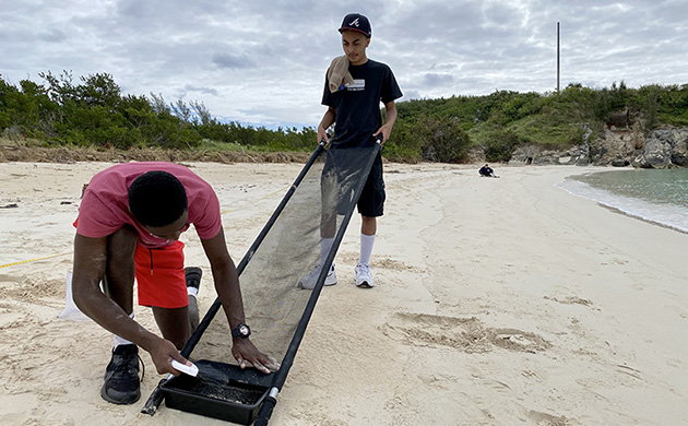 <p> Bermuda College student Jihad Muhammad (in black shirt) and intern Osei Agyapong collected microplastic samples then sifted them to sort plastics from sand, plants, rocks, and other organic materials. Muhammad and two other Bermuda College students participated in a weekly science program at BIOS this fall to continue learning that was disrupted by the pandemic.</p>